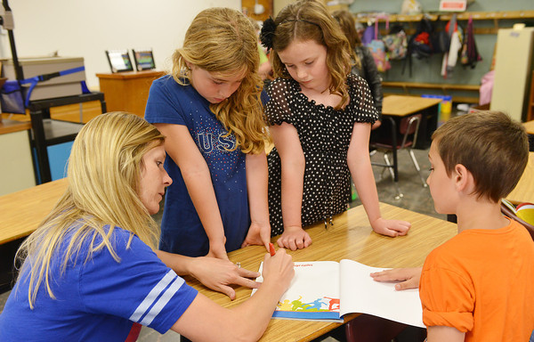 Globe/Roger Nomer<br /> The mood becomes somber towards the end of the school day as second-grade teacher Ashley Hobbs signs yearbooks for Kalei Campbell, Skyler Cheney and Jayce Stewart.
