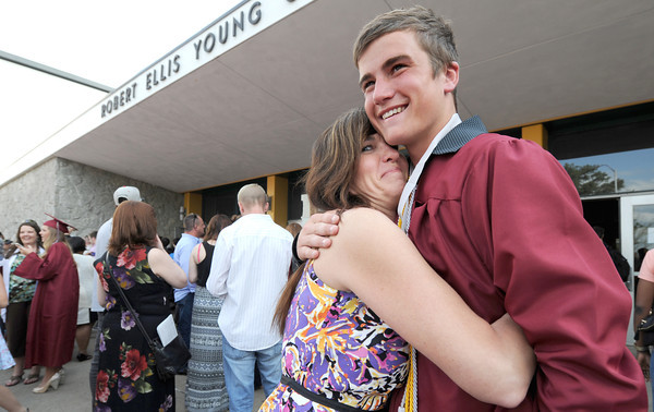 Kilty O'Connor-Box gets a hug from his mother, Valerie Box as loved ones await the arrival of their graduates outside Robert Ellis Young Gymnasium following graduation  ceremonies on Sunday at the Leggett & Platt Athletic Center.<br /> Globe | Laurie Sisk