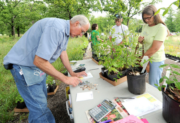 From the left: Mervin Wallace, of Missouri Wildflowers Nursery assists Phil Umphenour and Sheila Burns with their purchases at the Missouri Wildflower Nursery Native Plant Sale on Saturday at Wildcat Glades. A portion of the proceeds will go to benefit Wildcat Glades.<br /> Globe | Laurie Sisk