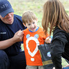 Neosho firefighter Wade Sterling, left and Children's Miracle Network Director Heather Lesmeister visits with four-year-old Thomas Perkins during a boot block in Neosho to benefit the Children's Miracle Network. Perkins was injured in an accident as a young toddler and received help from CMN.<br /> Globe | Laurie Sisk