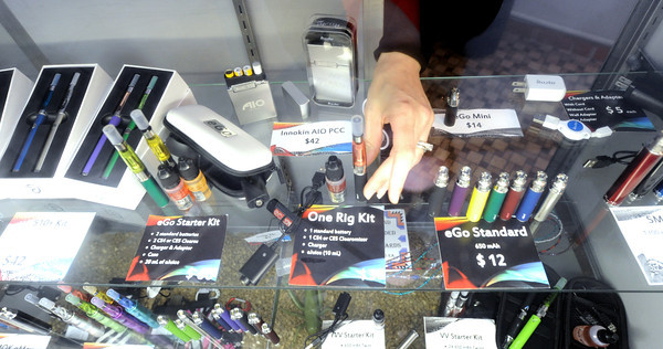 SWMO Vape Shop sales associate Amber Steele goes through a display case of numerous vape items on Friday at the store.<br /> Globe | Laurie Sisk