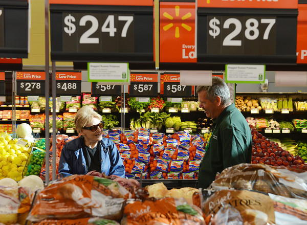 Globe/Roger Nomer<br /> Loris Crossley, Joplin, talks with Wal-Mart Associate Max Goldman in the produce aisle of the new Neighborhood Market on Thursday morning.