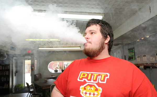 Matt Graham, Pittsburg, enjoys a draw off an electronic vaporizer on Friday at the SWMO Vape Shop.<br /> Globe | Laurie Sisk