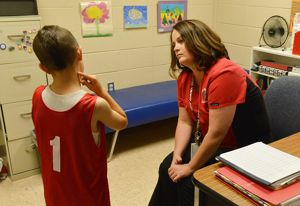 Globe/Roger Nomer<br /> Stacey Whitney talks with Mason Bickerstaff, first grade, during a visit to the nurse's office at Carl Junction Elementary on Thursday.