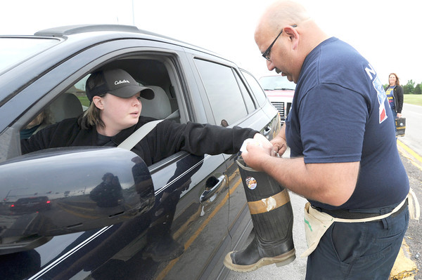 Neosho firefighter Al Cervantes collects a donation Friday from Sabrina Buzzard, of Diamond during a boot block in Neosho to benefit the Children's Miracle Network.<br /> Globe | Laurie Sisk