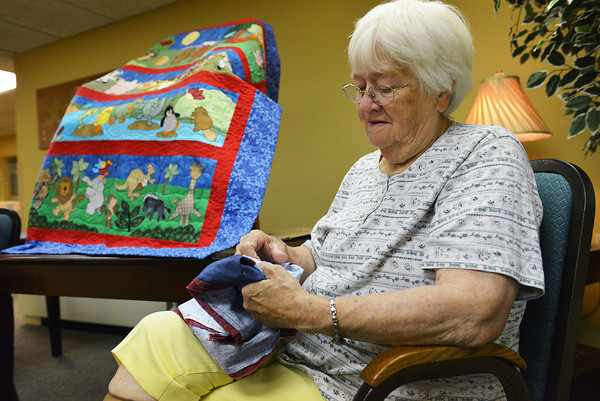 Globe/Roger Nomer<br /> Darlene LaGasse, with the Town and Country Quilters, takes time to sew during the Mother's Day quilt sale at Spring River Christian Village on Thursday afternoon. The sale feature over 80 quilts by club members and residents of the village.