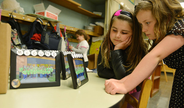 Globe/Roger Nomer<br /> Second graders Sarah Best and Skyler Cheney examine class photos of the entire student and teacher population of McCune Elementary on the last day of school. A parent made the frames for each student to take home.