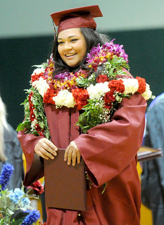 Joplin High School graduate Leilani Vaipalu is all smiles as she makes her way across the stage clad in colorful leis  during graduation ceremonies on Sunday at the Leggett & Platt Athletic Center. <br /> Globe   Laurie Sisk
