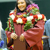 Joplin High School graduate Leilani Vaipalu is all smiles as she makes her way across the stage clad in colorful leis  during graduation ceremonies on Sunday at the Leggett & Platt Athletic Center. <br /> Globe | Laurie Sisk