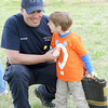 Neosho firefighter Wade Sterling visits with four-year-old Thomas Perkins during a boot block in Neosho to benefit the Children's Miracle Network. Perkins was injured in an accident as a young toddler and received help from CMN.<br /> Globe | Laurie Sisk