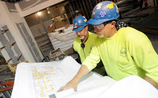 Scott Vandergrift, front and Todd Vandergrift, both of U.S. Engineering, look over schematics of the new Mercy Hospital on Wednesday. When completed, the hospital will contain about 3.7 million linear feet of wire and 2.5 million square feet of drywall.<br /> Globe | Laurie Sisk