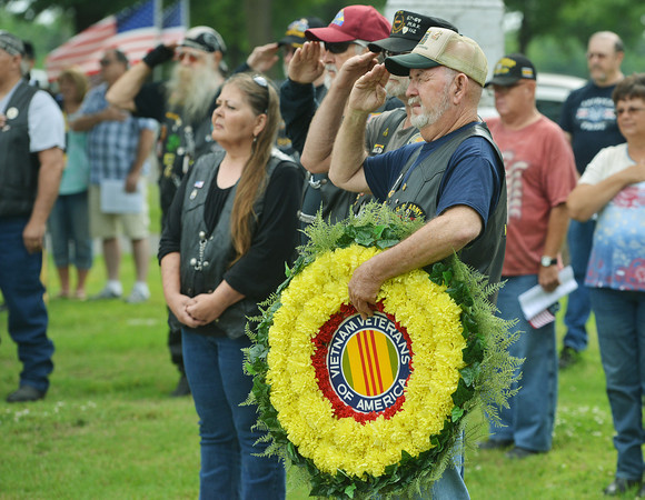 Globe/Roger Nomer<br /> Vietnam veteran Bill Southard, Miami, salutes while holding a wreath honoring fellow veterans during a Memorial Day ceremony at the Grand Army of the Republic Cemetery in Miami on Monday.