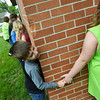 Globe/Roger Nomer<br /> Brett Drumiller, a second grader at McCune Elementary, checks around the corner as he hugs the building goodbye on Tuesday.
