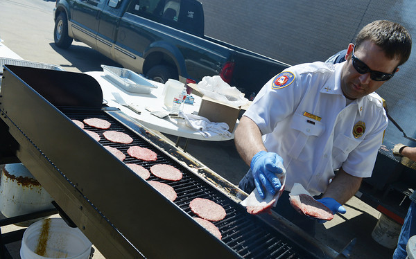 Globe/Roger Nomer<br /> Joplin Fire Captain John Alford grills hamburgers on Friday at Fire Station No. 1 during a fundraiser for Cade Cranford, 11 months. Cranford was recently diagnosed with retinoblastoma.