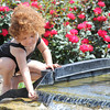 Against a backdrop of colorful flowers, Taliyah Walton, 4, rinses her hands in a waterfall at Cunningham PArk on Friday.<br /> Globe | Laurie Sisk