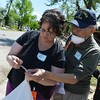Globe/Roger Nomer<br /> (from left) Sherry Tolle, Baxter Springs, Jim and Anita Leyba, Joplin, look over a photo found in tornado debris in Baxter Springs on Friday as they volunteer with National Disaster Photo Rescue. The Leybas has photos returned to them by the organization following the Joplin tornado.