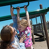 Globe/Roger Nomer<br /> Melissa Orahood helps her daughter Emily Culp, 6, onto the playground equipment at Cunningham Park on Thursday afternoon.
