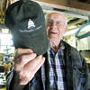 Eighty eight-year-old woodsmith Tom Rhoads proudly shows a cap from his son Mark's business, a consulting firm his son opened after years of public service, including serving as Deputy Director of the Department of Economic Development for Missouri. Rhoads fathered five extremely successful children including two doctors, a lawyer and an accomplished artist.<br /> Globe | Laurie Sisk