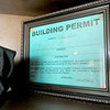 The first building permit issued after the May, 2011 tornado is displayed on a shelf at Cut Loose Salon.<br /> Globe | Laurie Sisk