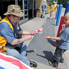 """U.S. Marine veteran Dan Riesdorph, of Southtown Post 5293 VFW, hands an American flag to six-year-old Jasper Grabe on Thursday at Walmart on Seventh street. Veterans were on hand Thursday, Friday and Saturday to hand out """"Buddy Poppies"""" and flags to raise money for needy local veterans. Riesdorph said the campaign raised about $5,000 for local veterans last year.<br /> Globe 