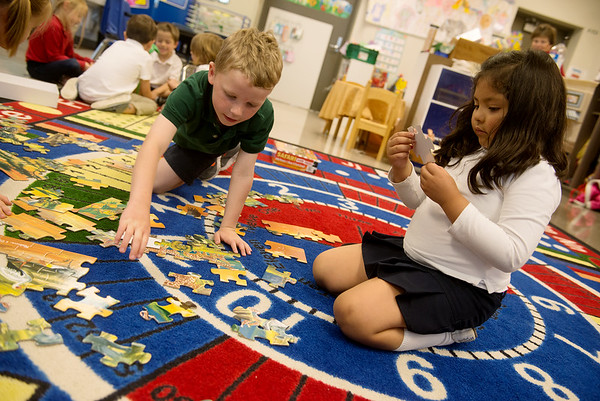 Globe/Roger Nomer<br /> St. Mary's kindergarten students Lucas Nangle and Miranda Alberto work on a puzzle during class on Thursday, April 14.
