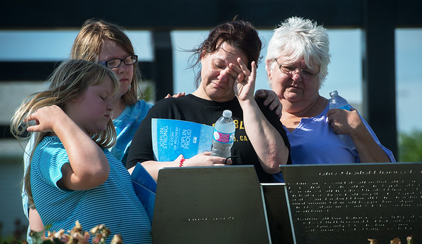 Globe/Roger Nomer<br /> Erin Baum wipes away a tear as she looks at a memorial with (from left) Ashleigh Smith, 10, Bayleigh Smith, 13, and Vicky Baum, her mother, on Sunday at Cunningham Park. Erin Baum's sister Heather Terry-Baum died in the 2011 tornado.