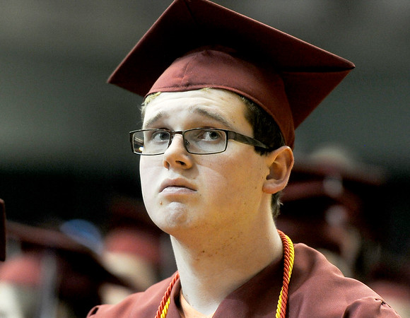 Joplin High School graduate Quinn Darby watches a tribute to classmates who have died during commencement ceremonies on Sunday at Leggett & Platt. Darby graduated as an A+ student.<br /> Globe | Laurie Sisk