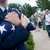 Globe/Roger Nomer<br /> Cadet Capt. Josiah Horn, with the Civil Air Patrol, holds a flag as visitors arrive for the Memorial Day ceremony at Mount Hope Cemetery on Monday.