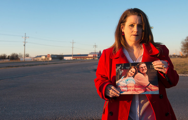 Globe/Roger Nomer<br /> Stacey Stevens holds a senior photo of her son Matthew at the intersection of Highway 59 and Malcolm Mosby Drive in Neoho, where he was killed in a hit and run.