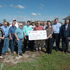 Globe/Roger Nomer<br /> The Joplin Regional Community Foundation presents the Joplin Area Fuller Center with a check to help with Eric Karraker's new home on Monday.
