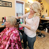 Stylist Alyssa Lawson styles client Lori Richard's hair at Cut Loose Salon. Lawson began working at the salon one year before the tornado.<br /> Globe | Laurie Sisk