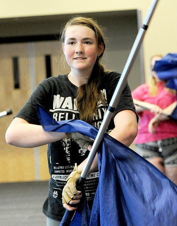 Joplin High School's Hailey Stamper rehearses with the color guard on Tuesday at JHS for an upcoming appearance in the Memorial Day Parade in Washington D.C. on Monday. Stamper created buttons honoring loved ones for bandmembers to wear as they march.<br /> Globe | Laurie Sisk