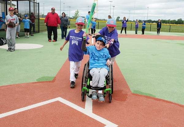 Globe/Roger Nomer<br /> Konner Head, 7, and Trenton Fast, 9, both of Webb City, help Treyton Ritchhart, 8, across home plate during a game on Saturday, April 30, at the Will Norton Miracle Field. Volunteers buddy up with players, which lets everyone join in the fun of playing ball at the field.