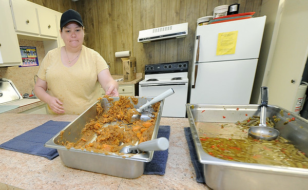 Krista Dardene, site manager for the Southeast Kansas Area Agency on Aging, cleans up after preparing more than 50 meals for Baxter Springs and Galena clients on Wednesday at the Baxter Springs Community Building.<br /> Globe   Laurie Sisk