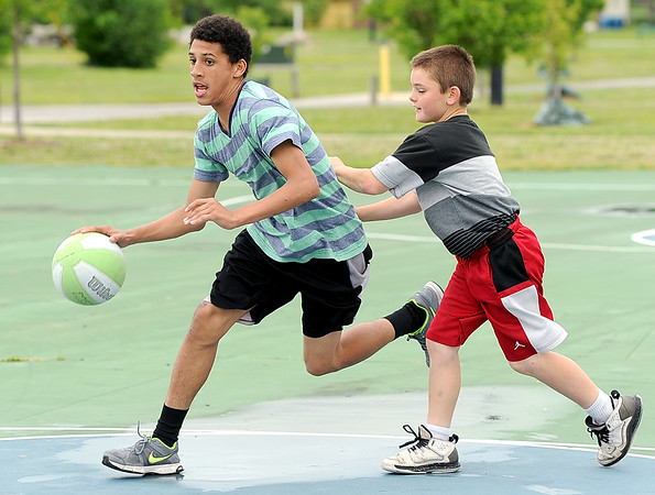 Fourteen-year-old Kobe Harrison, left and Ashton Anderson, 10, don't let chilly temperatures keep them from enjoying summer break as they engage in a spirited game of basketball on Tuesday afternoon at Parr Hill Park.<br /> Globe | Laurie Sisk