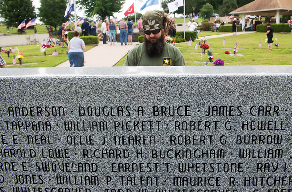 Globe/Roger Nomer<br /> Brad Cooksey, Normal, Ill., reads names at the Veterans Memorial at Mount Hope Cemetery on Monday.