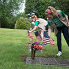 Globe/Roger Nomer<br /> Girl Scout cadets Abbey Cahalan, 12, left, and Ava Gould, 12, from Troop 26258, place flags on veteran graves at Mt. Hope Cemetery on Friday.