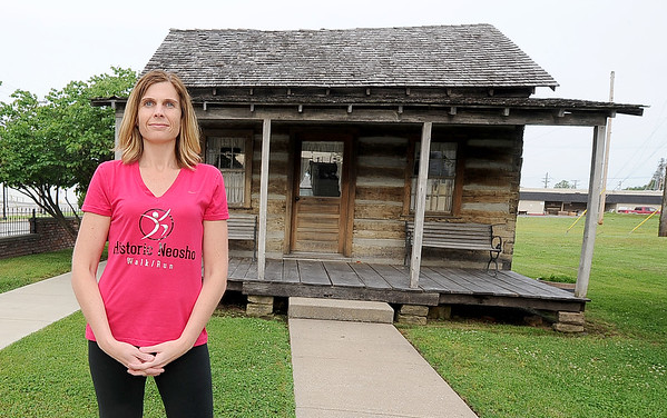 Ashley Scroggins stands outside an old cabin that is part of the Historic Walk/Run Tours Scroggins hosts in Neosho.<br /> Globe | Laurie Sisk