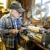 Eighty eight-year-old woodsmith Tom Rhoads tools a template of a gavel on his lathe inside his workshop on Tuesday. Most items in his home made of wood were created by Rhoads.<br /> Globe | Laurie Sisk