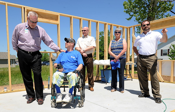Habitat for Humanity  board chairman Fred Osborn visits with future homeowner Travis Vene during ceremonies on Friday afternoon for Vene's new barrier-free home at 2106 Virginia on Tuesday. Vene, who is paralyzed from the waist down, will soon inhabitat the home, which will feature a roll-in shower, lower cabinets and high electrical sockets, among other features designed around a wheel chair bound resident. Thrivent Financial supplied a $40,000 grant to help build the home. It is the ninth Joplin home that the company has helped build. The Independent Living Center consulted on the design of the home. Also pictured from the left:  Habitat board member Larry Warren, Kris Callen , of Thrivent Financial and Scott Clayton, executive director of Joplin Habitat for Humanity.<br /> Globe | Laurie Sisk