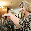 "Stylist Kimberly Hoover works on a customer's hair at Cut Loose Salon. Hoover has been working with salon owner Dianna Collins for 23 years and said it was ""no decision"" on whether to return after the rebuilding of the salon.<br /> Globe 