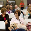 Globe/Roger Nomer<br /> Jenny Wiley, Liberty, Mo., looks at photos of natural disasters during Thursday's Joplin Disaster Recovery Summit at Missouri Southern. Wiley works with Pet Partners and brought therapy dog Yogi with her to the seminar.