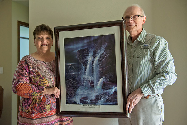 """Globe/Roger Nomer<br /> Naomi and John Hunter display the Jack Dawson painting """"Peace in the Midst of the Storm"""" which survived the 2011 tornado in their previous house."""