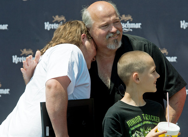 Globe/Roger Nomer<br /> Richard Gray gets a hug from his father Richard Gray as nephew Wayne Baker, 9, looks on after the delivery of the restored truck on Friday at Price Cutter in Joplin.