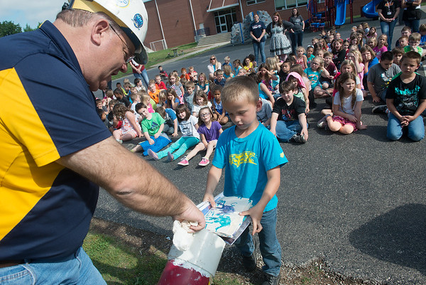 Globe/Roger Nomer<br /> Rick Stockton, senior construction designer with Empire, helps Jefferson Elementary kindergartner Bo Abell place an item in the new time capsule on Tuesday.