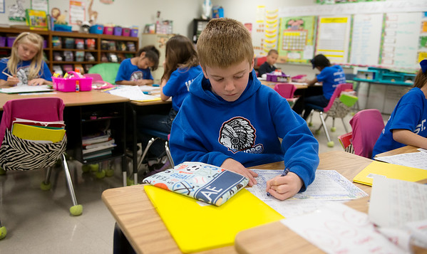 Globe/Roger Nomer<br /> St. Mary's Elementary second grader Trae Veer works on an assignment on Thursday, April 14.