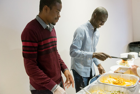 Globe/Roger Nomer<br /> Michael Mwale, a Crowder freshman from Zambia, left, and Kande Keve, a freshman from Mali, serve food during Monday's International Food Festival at Crowder College.