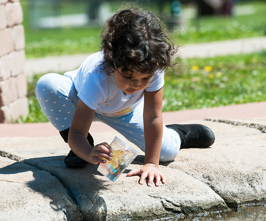 Three-year-old Daelynn Walker uses a cup to seek out minnows on a sunny day Tuesday afternoon at Cunningham Park. After a break Tuesday from rainy weather, more storms are expected in the area on Wednesday.<br /> Globe   Laurie Sisk