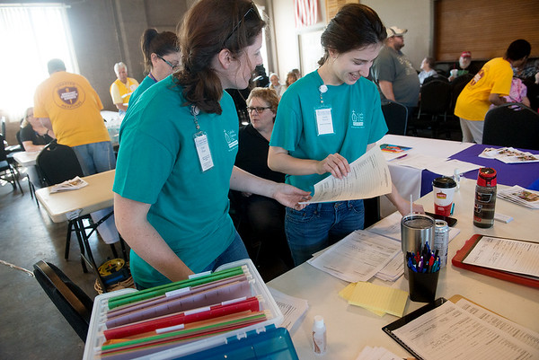 Globe/Roger Nomer<br /> Gabi Hane, left, and Judith Beaver set up a booth for Catholic Charities of Southern Missouri at a help center in the Lampo Building in Neosho on Monday.