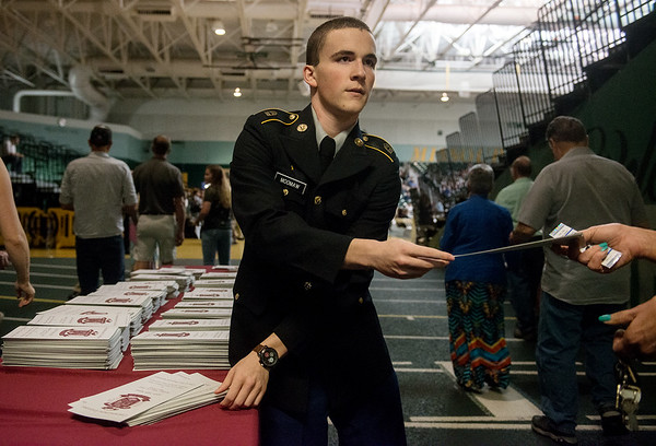 Globe/Roger Nomer<br /> Joplin High JROTC member Anthony Moomaw, sophomore, hands out programs for graduation on Sunday at the Leggett and Platt Athletic Center.